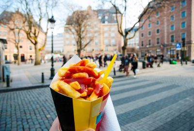 A paper-bag with french fries in front of old houses in Brussels