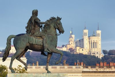 A statue of King Louis XIV and the Basilica of Notre-Dame de Fourvière at the background