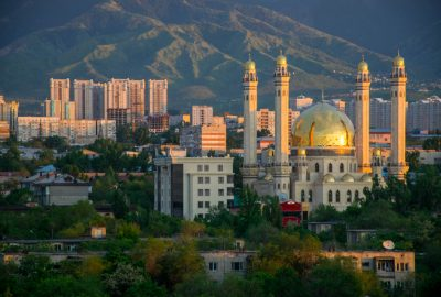 Almaty Central Mosque to the backdrop of mountains and skyscrapers