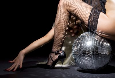 Dancer sitting on shiny disco ball in Beirut night club