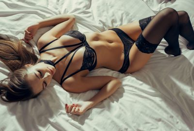 Independent Berlin escort in black lingerie stretching out on bed