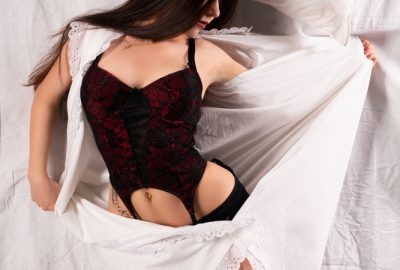 Beautiful Budapest escort wearing black lingerie and wrapped in white sheets