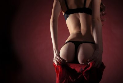 Stripper taking off her clothes in Ghent striptease club
