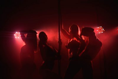 Dancers in dimmed red lights on stage in Helsinki striptease club