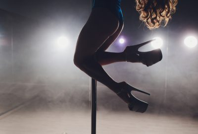Girl swinging around a pole in striptease club in Nice
