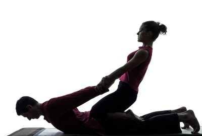 Girl stretching arms of man during sports massage session