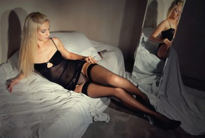 Blonde escort in Thessalonik posing on bed in private apartment