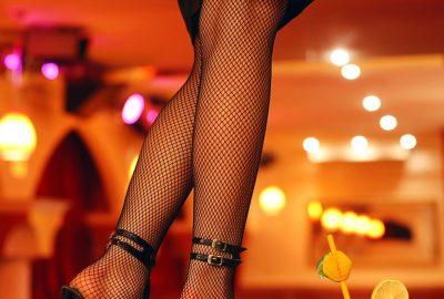 Girl in fishnet stockings on high heels in Abu Dhabi bar