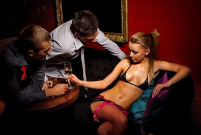 Male visitors flirting with dancer in Odessa striptease club