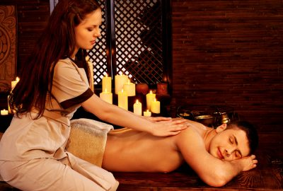 Man receiving a back massage in romantic setting of massage studio in Palma de Mallorca
