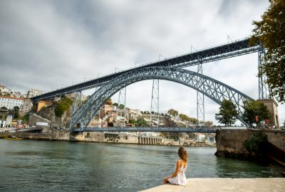 Girl sitting at the bank of the Douro river and looking at the Bridge Dom Luis I in Porto
