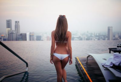 Escort in Singapore at rooftop swimming pool looking at the city skyline