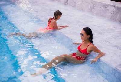 Two girls relaxing in outdoor swimming pool of FKK sauna club in Zurich