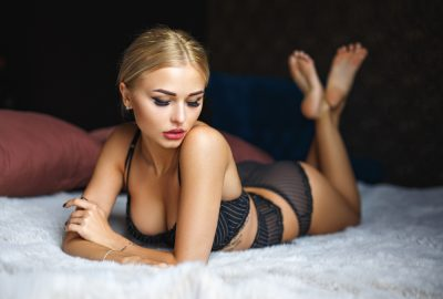 Blonde Zurich escort at bed in black lingerie