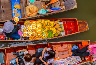 Locals in Bangkok selling fruits on boats at the floating market of Damnoen Saduak