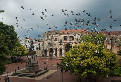 Parque Colon in Santo Domingo with Cathedral and Columbus statue visited by flock of pingeons