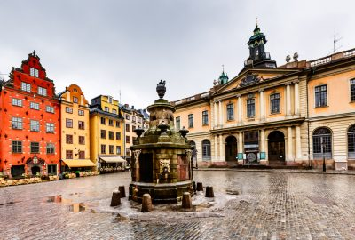 Stortorget square with fountain flanked by colourful facades of medieval houses in Gamla Stan, the Old Town of Stockholm