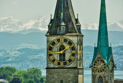 The towers of the Fraumunster and St. Peter Church in Zurich with the snow tops of the Swiss Alps at the background