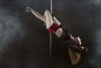 Dancer swinging around pole in Dubrovnik striptease club