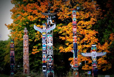 Totem poles in in autumn foliage of Stanley Park in Vancouver