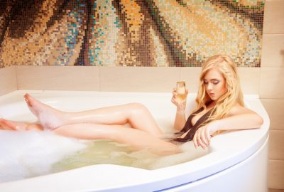 Girl sipping champagne in Jacuzzi in massage salon in Cannes