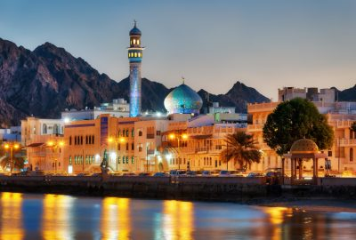 Muttrah Corniche in Muscat by evening with illuminated mosque and mountains to the backdrop