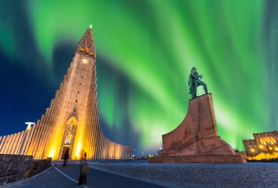 Hallgrimskirkja Cathedral and statue of Leifur Eiríksson in Reykjavik to the backdrop of the Northern Lights