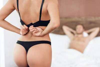 Reykjavik escort undressing in front of client, eagerly waiting in bed