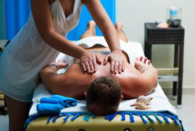Male client getting back and shoulders massage in salon in Liege