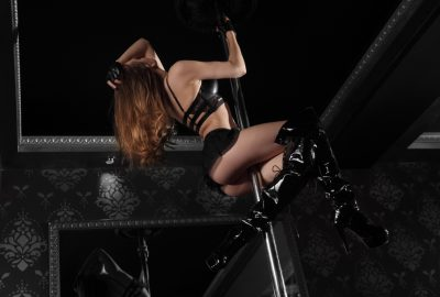 Dancer in long black latex boots climbing in pole in Marseille strip club