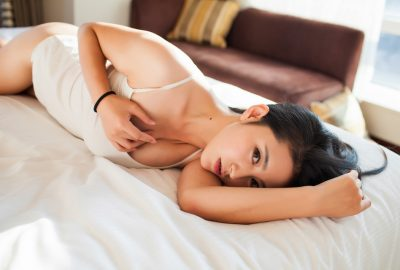 Sexy Chinese masseuse stretching out on bed