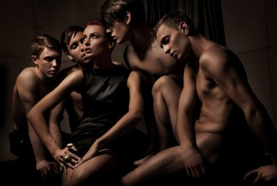Female guest of Vancouver swinger clubs surrounded by male woreshippers