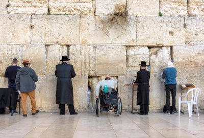 People standing at the Wailing Wall in Jerusalem