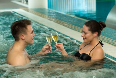 Couple sipping champagne and relaxing in whirlpool of FKK club in Basel
