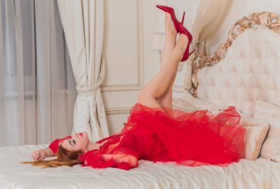 Beautiful Jerusalem escort in red dress and high heel shoes posing on bed