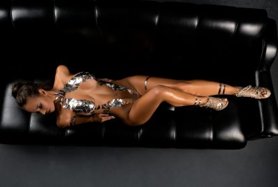 Canberra escort in sexy pose on black leather sofa